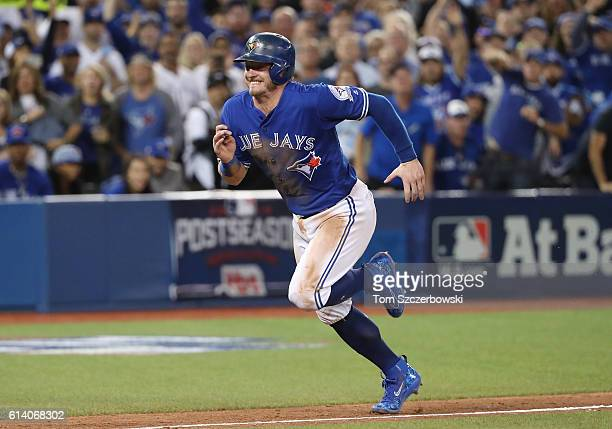 Josh Donaldson of the Toronto Blue Jays races home to score the gamewinning run in the tenth inning during MLB game action against the Texas Rangers...