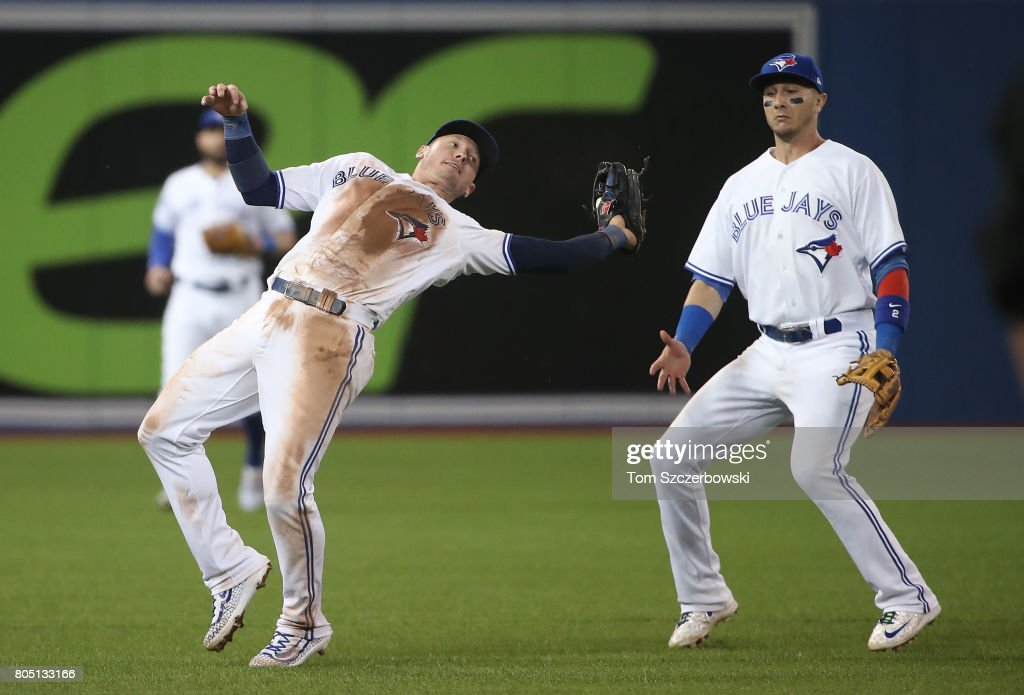Josh Donaldson #20 of the Toronto Blue Jays reaches over his shoulder to catch a pop up as Troy Tulowitzki #2 watches in the ninth inning during MLB game action against the Boston Red Sox at Rogers Centre on June 30, 2017 in Toronto, Canada.