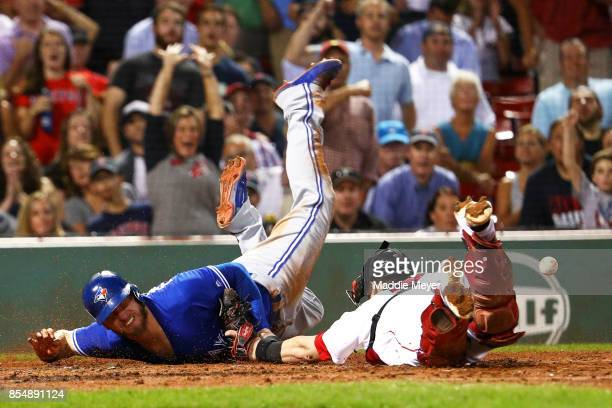 Josh Donaldson of the Toronto Blue Jays slides past Christian Vazquez of the Boston Red Sox to score a run during the third inning at Fenway Park on...