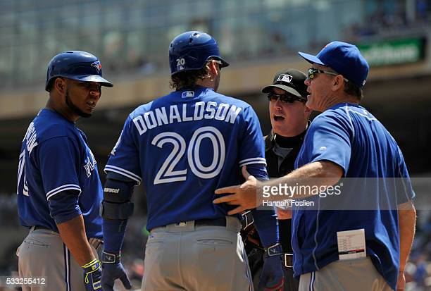Josh Donaldson of the Toronto Blue Jays speaks with home plate umpire Toby Basner after being tossed as teammate Edwin Encarnacion and manager John...