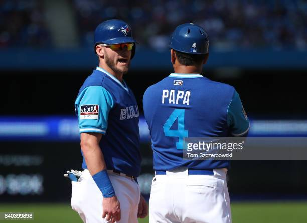 Josh Donaldson of the Toronto Blue Jays talks to third base coach Luis Rivera as he stands on third base in the eighth inning during MLB game action...