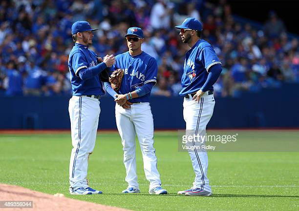 Josh Donaldson Ryan Goins and Chris Colabello of the Toronto Blue Jays chat in the seventh inning during a MLB game against the at Rogers Centre on...