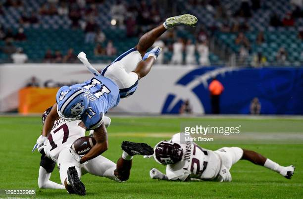 Josh Downs of the North Carolina Tar Heels dives over Jaylon Jones of the Texas A&M Aggies after making a catch in the first half of the Capital One...