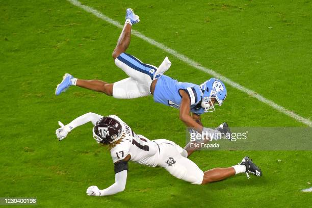 Josh Downs of the North Carolina Tar Heels is upended by Jaylon Jones of the Texas A&M Aggies during the first quarter of the Capital One Orange Bowl...
