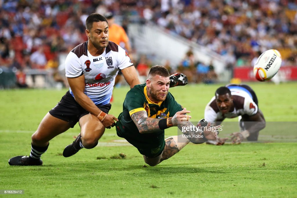 Josh Dugan of Australia passes as he is tackled by Jarryd Hayne of Fiji during the 2017 Rugby League World Cup Semi Final match between the Australian Kangaroos and Fiji at Suncorp Stadium on November 24, 2017 in Brisbane, Australia.