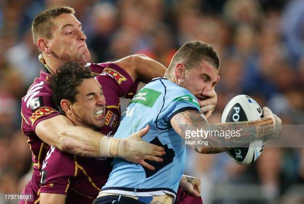 Josh Dugan of the Blues is tackled by Billy Slater and Brent Tate of the Maroons during game three of the ARL State of Origin series between the New...