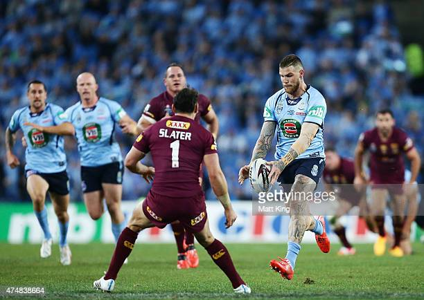 Josh Dugan of the Blues makes a break and kicks ahead for the try to Josh Morris during game one of the State of Origin series between the New South...