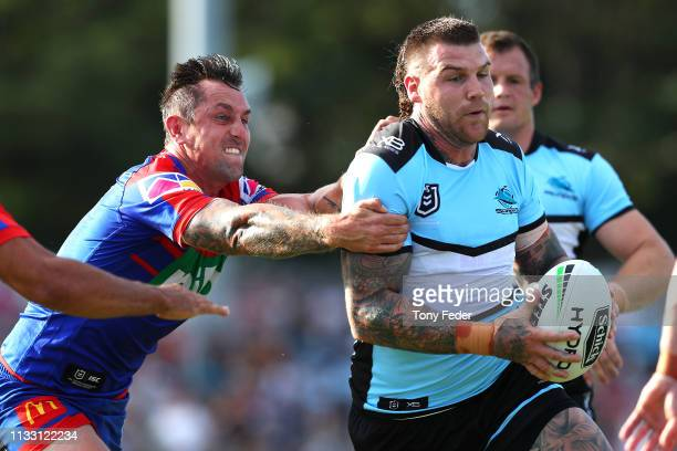Josh Dugan of the Cronulla Sharks is tackled by Mitchell Pearce of the Newcastle Knights during the NRL Trial match between the Cronulla Sharks and...