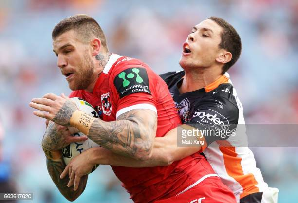 Josh Dugan of the Dragons is tackled by Mitchell Moses of the Tigers during the round five NRL match between the Wests Tigers and the St George...