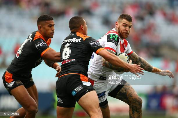 Josh Dugan of the Dragons is tackled during the round 13 NRL match between the St George Illawarra Dragons and the Wests Tigers at ANZ Stadium on...