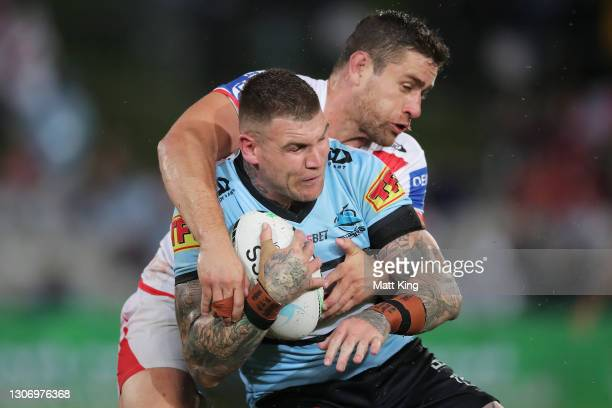 Josh Dugan of the Sharks is tackled by Andrew McCullough of the Dragons during the round one NRL match between the St George Illawarra Dragons and...