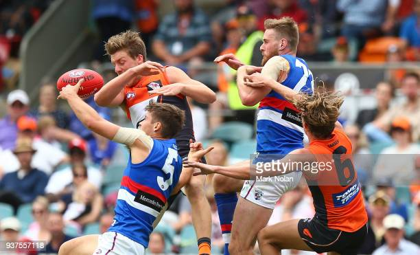 Josh Dunkley Jordan Roughead of the Bulldogs and Lachie Whitfield of the Giants contest possession during the round one AFL match between the Greater...