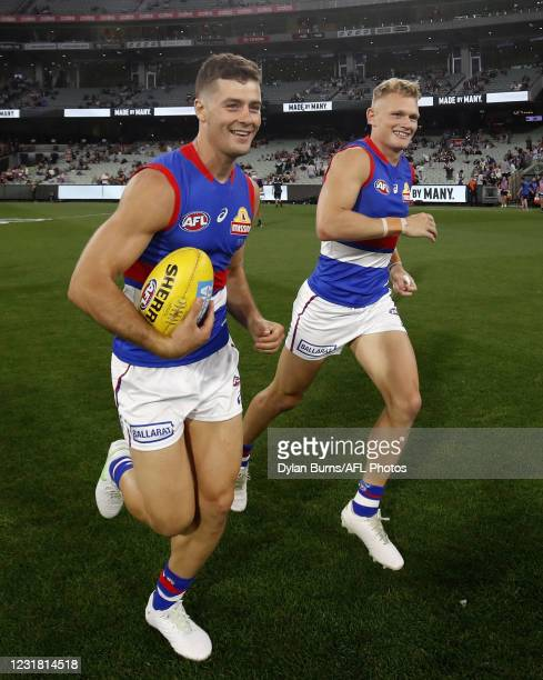 Josh Dunkley of the Bulldogs and Adam Treloar of the Bulldogs enter the field during the 2021 AFL Round 01 match between the Collingwood Magpies and...
