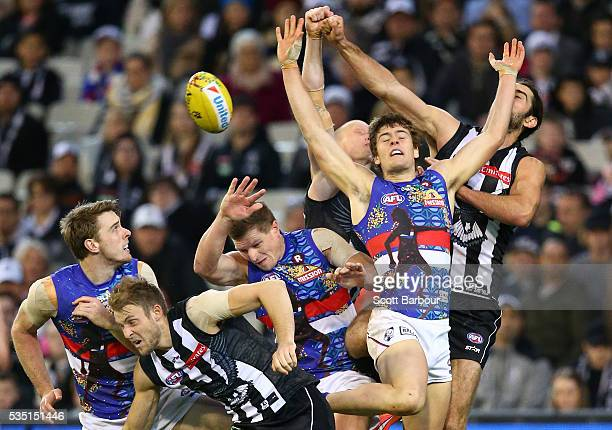 Josh Dunkley of the Bulldogs and Brodie Grundy of the Magpies and Ben Reid of the Magpies compete for the ball during the round 10 AFL match between...