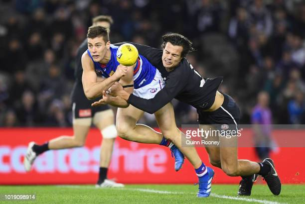 Josh Dunkley of the Bulldogs handballs whilst being tackled by Jack Silvagni of the Blues during the round 22 AFL match between the Carlton Blues and...