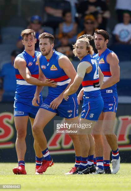 Josh Dunkley of the Bulldogs is congratulated by Marcus Bontempelli and Easton Wood of the Bulldogs after kicking a goal during the AFL JLT Community...