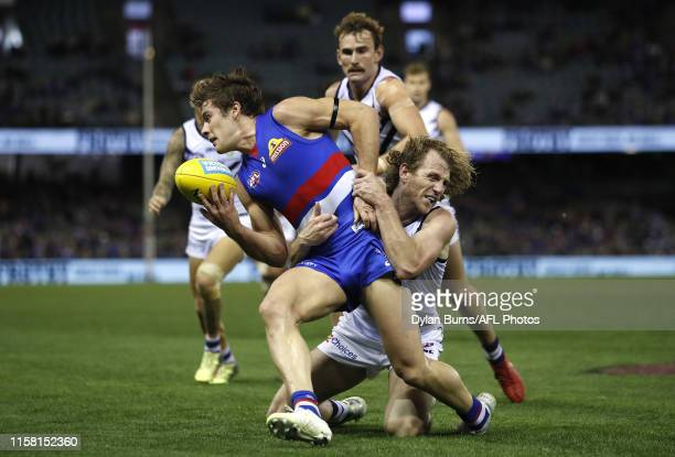 Josh Dunkley of the Bulldogs is tackled by David Mundy of the Dockers during the 2019 AFL round 19 match between the Western Bulldogs and the...