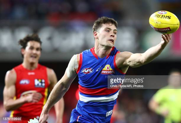 Josh Dunkley of the Bulldogs looks to control the ball during the round 18 AFL match between Gold Coast Suns and Western Bulldogs at Metricon Stadium...