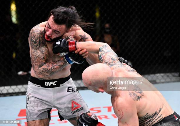 Josh Emmett punches Shane Burgos in their feathweight bout during the UFC Fight Night event at UFC APEX on June 20 2020 in Las Vegas Nevada