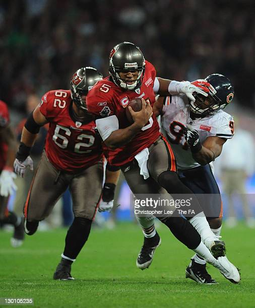 Josh Freeman of the Tampa Bay Buccaneers evades the tackle of Amobi Okoye of the Chicago Bears during the NFL International Series match between...