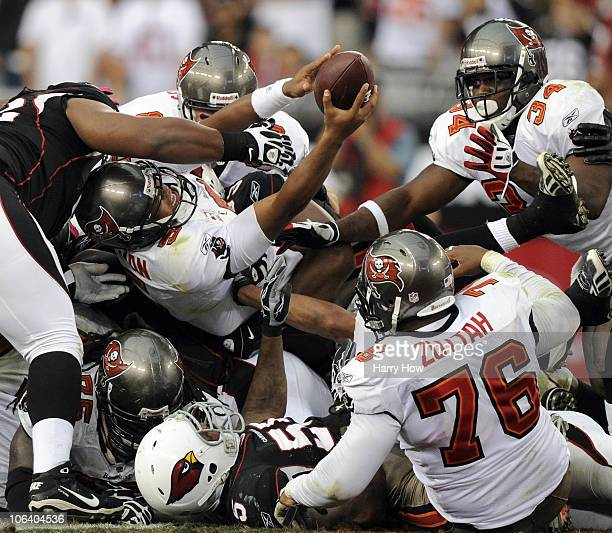 Josh Freeman of the Tampa Bay Buccaneers reaches with the ball for a first down on a quarterback sneak play on fourth down in front of Earnest Graham...
