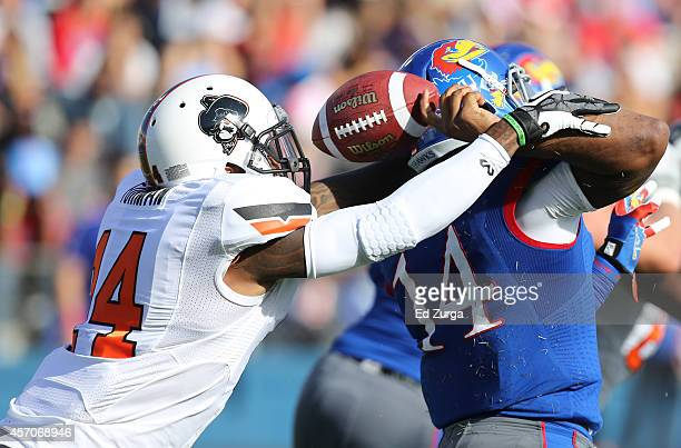 Josh Furman of the Oklahoma State Cowboys strips the ball from quarterback Michael Cummings of the Kansas Jayhawks in the first quarter at Memorial...