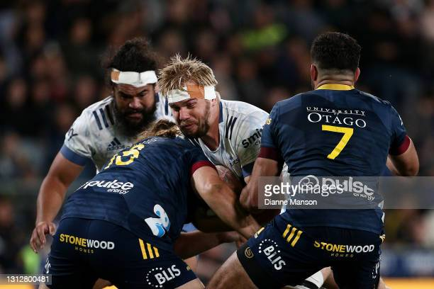 Josh Goodhue of the Bluesis tackled by Josh Hohneck and Billy Harmon of the Highlanders during the round eight Super Rugby Aotearoa match between the...