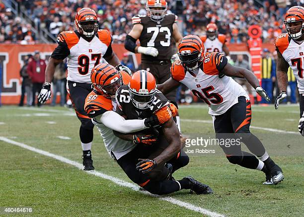 Josh Gordon of the Cleveland Browns gets tackled by Carlos Dunlap and Wallace Gilberry of the Cincinnati Bengals during the second quarter at...