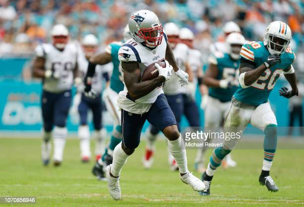Josh Gordon of the New England Patriots carries the ball durig the second half against the Miami Dolphins at Hard Rock Stadium on December 9 2018 in...