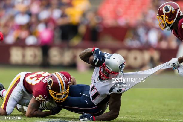 Josh Gordon of the New England Patriots gets his jersey torn by Josh Norman of the Washington Redskins as he is tackled by Quinton Dunbar during the...