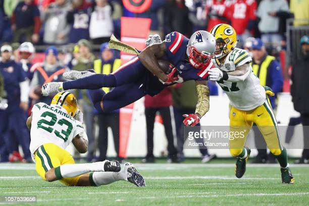 Josh Gordon of the New England Patriots is tackled by Jaire Alexander and Josh Jones of the Green Bay Packers during the second half at Gillette...