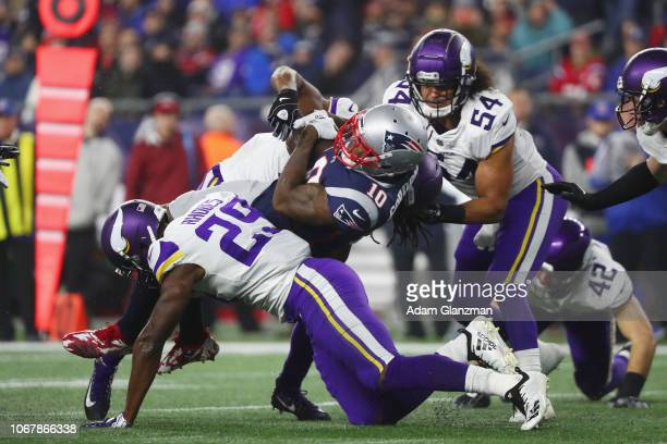 Josh Gordon of the New England Patriots is tackled by Xavier Rhodes and Eric Kendricks of the Minnesota Vikings during the second half at Gillette...