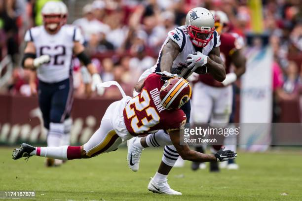Josh Gordon of the New England Patriots stiff arms Quinton Dunbar of the Washington Redskins during the first half at FedExField on October 6 2019 in...