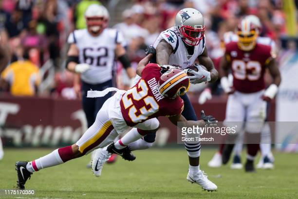 Josh Gordon of the New England Patriots stiffarms Quinton Dunbar of the Washington Redskins during the first half at FedExField on October 6 2019 in...