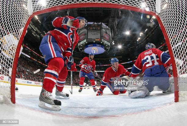 Josh Gorges Mike Komisarek and Steve Begin of the Montreal Canadiens support teammate Carey Price in the crease against the Boston Bruins during game...