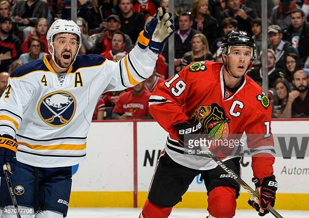 Josh Gorges of the Buffalo Sabres and Jonathan Toews of the Chicago Blackhawks watch for the puck during the NHL game on October 11 2014 at the...