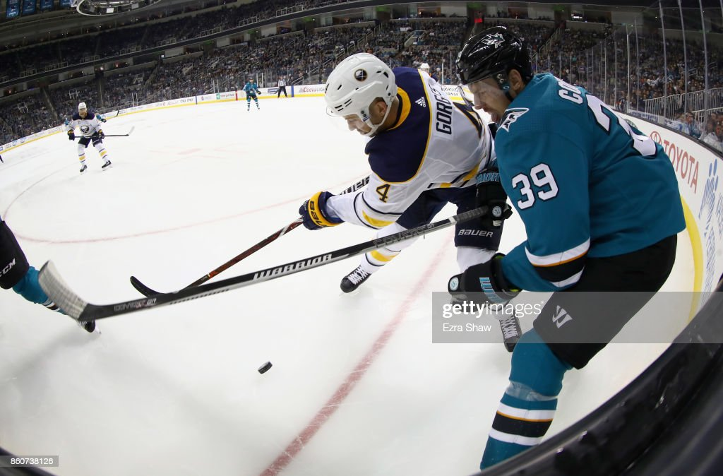 Josh Gorges #4 of the Buffalo Sabres and Logan Couture #39 of the San Jose Sharks go for the puck at SAP Center on October 12, 2017 in San Jose, California.