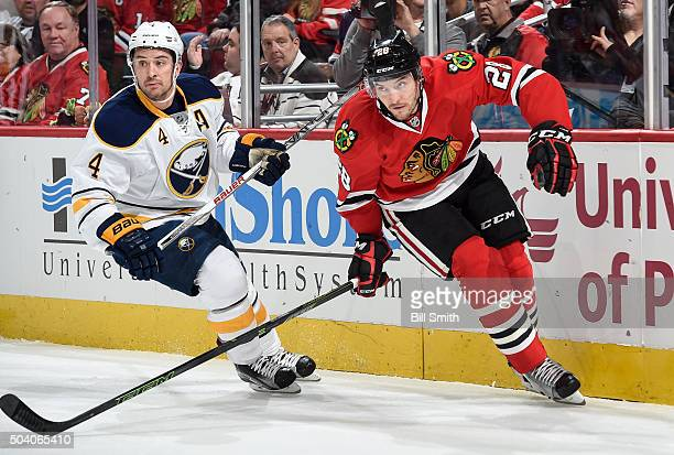 Josh Gorges of the Buffalo Sabres and Ryan Garbutt of the Chicago Blackhawks skate around the boards in the first period of the NHL game at the...