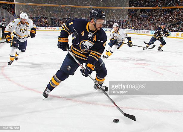 Josh Gorges of the Buffalo Sabres controls the puck as Mike Fisher and Colin Wilson of the Nashville Predators approach during an NHL game on...