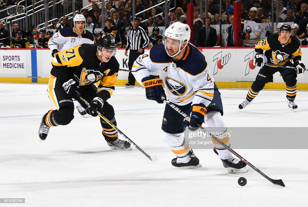 Josh Gorges #4 of the Buffalo Sabres moves the puck in front of Evgeni Malkin #71 of the Pittsburgh Penguins at PPG Paints Arena on November 14, 2017 in Pittsburgh, Pennsylvania.