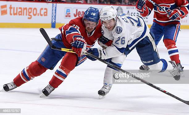 Josh Gorges of the Montreal Canadiens and Martin St Louis of the Tampa Bay Lightning battle for the puck during the NHL game on February 1 2014 at...