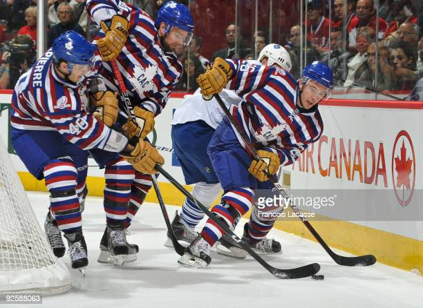 Josh Gorges of the Montreal Canadiens and teammates Guillaume Latendresse and Maxim Lapierre battle for the puck during the NHL game against the...