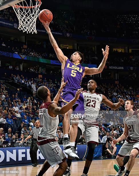 Josh Gray of the LSU Tigers takes a shot over Anthony Collins and Danuel House of the Texas AM Aggies during the first half of an SEC Basketball...