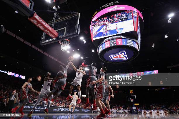 Josh Green of the Arizona Wildcats attempts a shot over Lahat Thioune of the Utah Utes during the first half of the NCAA men's basketball game at...