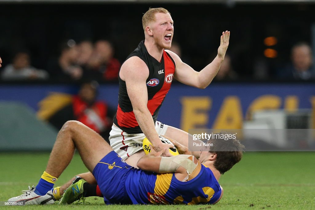Josh Green of the Bombers questions the umpire after being tackled by Andrew Gaff of the Eagles during the round 14 AFL match between the West Coast Eagles and the Essendon Bombers at Optus Stadium on June 21, 2018 in Perth, Australia.