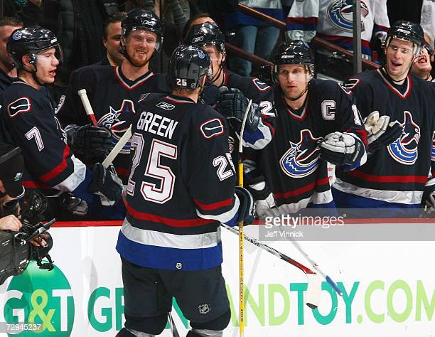 Josh Green receives congratulations from Markus Naslund of the Vancouver Canucks as he skates to the bench following a goal against the Florida...