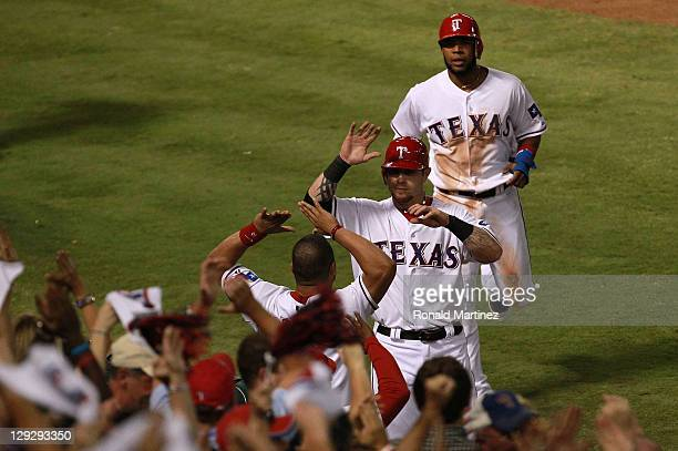 Josh Hamilton and Elvis Andrus of the Texas Rangers jog to the dugout after scoring in the third inning to tie Game Six of the American League...