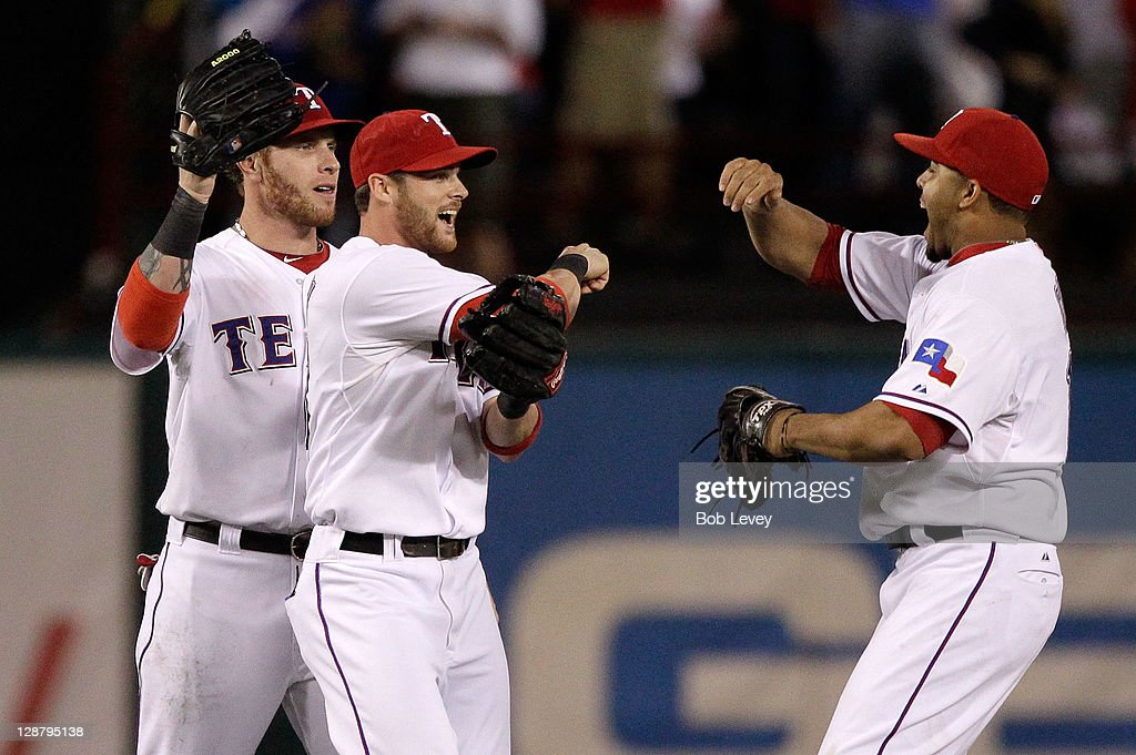 Josh Hamilton #32, Craig Gentry #23, and Nelson Cruz #17 of the Texas Rangers celebrates their 3-2 win over the Detroit Tigers in Game One of the American League Championship Series at Rangers Ballpark in Arlington on October 8, 2011 in Arlington, Texas.