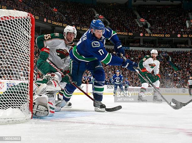 Josh Harding and Nick Schultz of the Minnesota Wild look on as Ryan Kesler of the Vancouver Canucks grabs a rebound during their NHL game at Rogers...