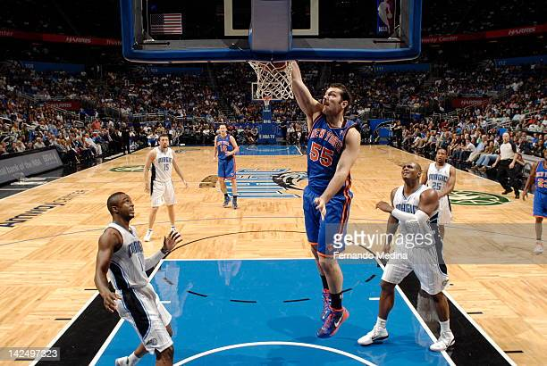 Josh Harrellson of the New York Knicks dunks over Von Wafer and Glen Davis of the Orlando Magic on April 5 2012 at Amway Center in Orlando Florida...